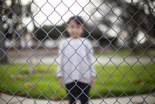 Boy Standing Behind The Fence