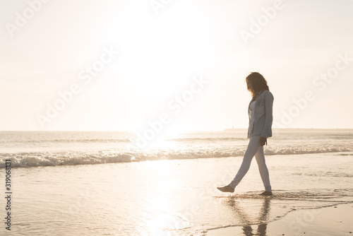 Full Length Of Woman Walking At Beach Against Sky During Sunset