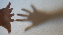 Close-Up Of Hand Gesturing Against Wall
