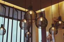 Low Angle View Of Illuminated Pendant Lights Hanging On Ceiling