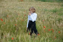 Girl Holding Poppy While Stand...
