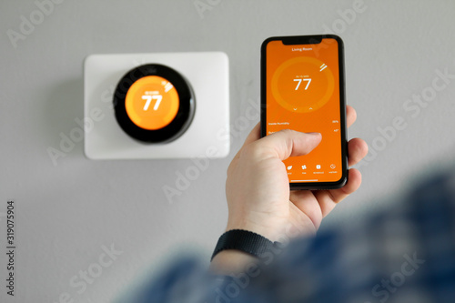 Man uses a mobile phone with smart home app in modern living room Fototapeta