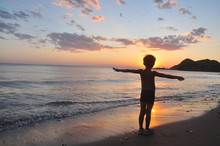 Full Length Of Boy With Arms Outstretched Standing On Shore At Beach During Sunset