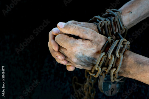 Photo Hands of a humble slave who is not trying to free himself against a dark backgro