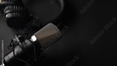 Cuadros en Lienzo Studio black studio microphone with studio headphones on a black background
