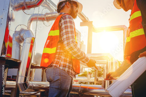 Fotomural Architect and engineer construction workers consulting and discuss while working at cooling machine factory