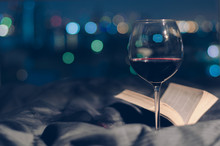 A Glass Of Red Wine Put On Bed With Book And Colorful Bokeh From City Lights Background.