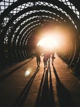 People Walking In Covered Bridge During Sunset