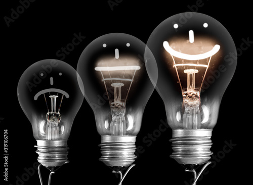 Fototapeta Dark and Shining Light Bulbs with Positive and Negative Emotion obraz