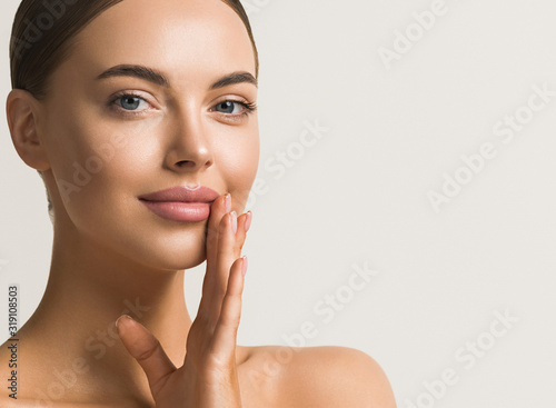 Fotografía Beautiful woman face close up natural make up hand touching face beauty smile