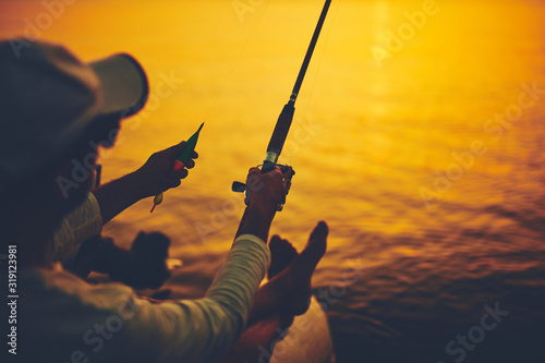 Photo Silhouette of a fisherman fishing in sunset time on the open sea.