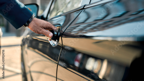 Photographie Cropped photo of a male hand opening the door of a black car while standing outd