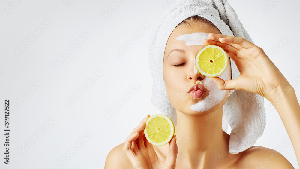 Fototapeta Cosmetology, skin care, face treatment, spa and natural beauty concept. Woman with facial mask holds lemons.