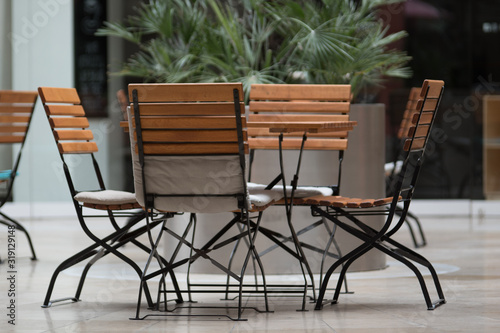 Obraz Empty Chairs And Table On Floor In Restaurant - fototapety do salonu
