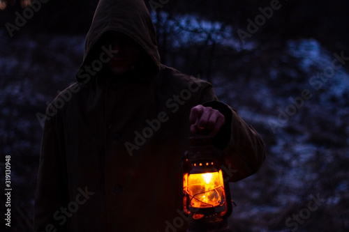 a man with an old glowing lantern in a raincoat in a dark forest Canvas Print