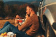 canvas print picture - Beautiful young couple enjoying picnic time on the sunset. They drinking tea and sitting in a meadow leaning on old fashioned car.