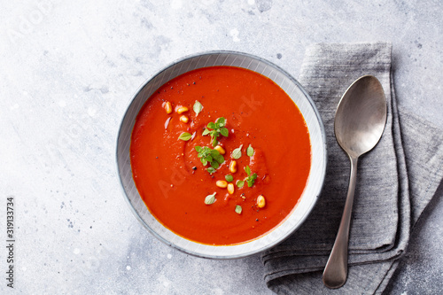 Fototapeta Tomato soup with fresh herbs and pine nuts in a bowl. Grey stone background. Top view. obraz