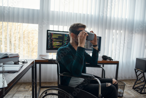 фотография Young male web developer in a wheelchair wearing virtual reality glasses while working at his workplace in modern office