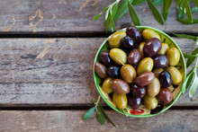 Assortment Of Fresh Olives On A Plate With Olive Tree Brunches. Wooden Background. Top View. Copy Space.