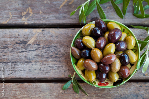 Photo Assortment of fresh olives on a plate with olive tree brunches