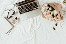 Fashion, Beauty, Lifestyle Blogger Home Office Workspace. Laptop, Roses Bouquet, Women's Accessories On White Linen. Flat Lay, Top View Woman Work Concept.