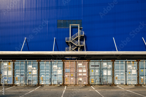Valokuvatapetti View of many shipping containers doors with fire escape background