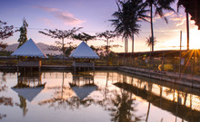 Reflection Of Gazebos In Pond During Sunset