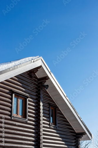 Modern log house in winter against a blue sky Wallpaper Mural