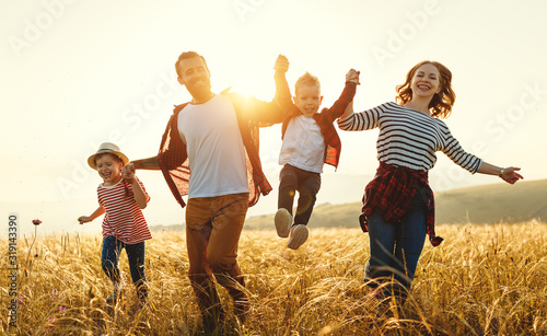 Obraz Happy family father of mother and child son  on nature at sunset - fototapety do salonu