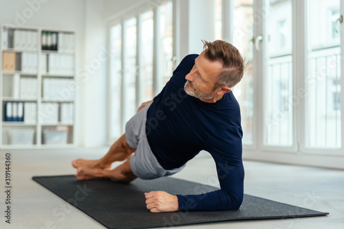 Fototapeta Middle-aged man working out doing side stretches obraz