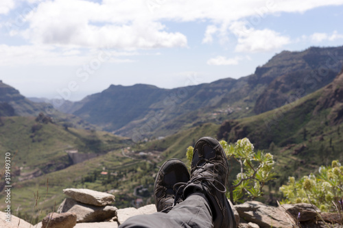Low Section Of Person Relaxing On Mountain Against Sky