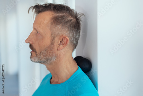 Photo Middle-aged man using a massage roller