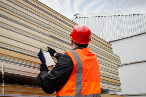 A worker in a protective helmet and overalls makes an inventory of sandwich panels and writes information in his notebook Canvas Print
