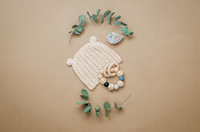 Wooden Teether And Baby Hat On Beige Background