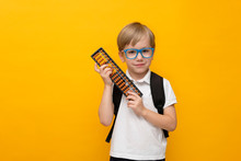 Cute Little School Boy In Glasses Holding Abacus On Yellow Background. Mental Arithmetic