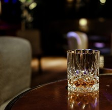 Crystal Whisky Glass On Round Wooden Table In Luxury Lounge