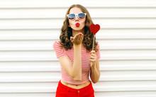 Portrait Beautiful Young Woman With Red Heart Shaped Sunglasses Blowing Lips Sending Sweet Air Kiss On White Wall Background