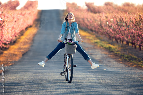 Pretty young woman with a vintage bike enjoying the time in cherry field in springtime. #319165709
