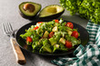 Salad with avocado, lettuce, tomato and flax seeds on gray background