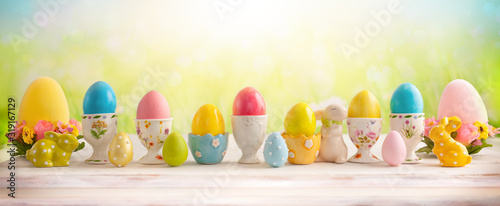 Photo Easter concept with colorful decorated eggs in egg cups and flowers