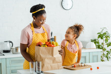 Happy African American Kid Looking At Mother Near Groceries