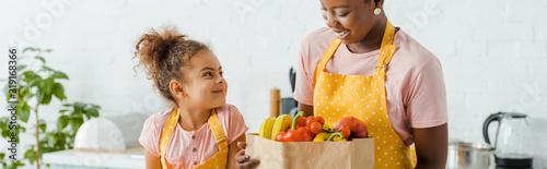 Fototapeta panoramic shot of happy african american kid looking at mother near groceries obraz