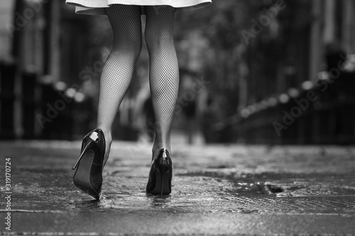 Obraz na plátne Low Section Of Woman Walking On Wet Road