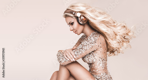 Beautiful young woman in headphones listening to music smiling with closed eyes standing on a beige background. Elegant girl in disco evening dress