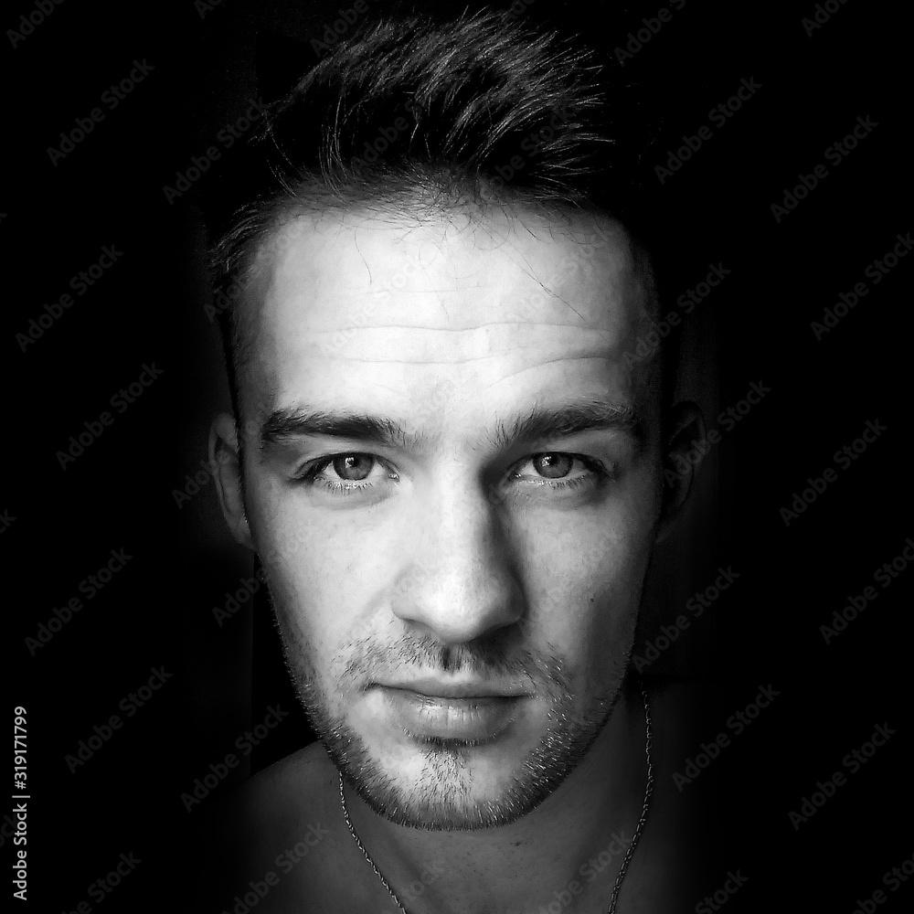 Fototapeta Portrait Of Young Man Against Black Background