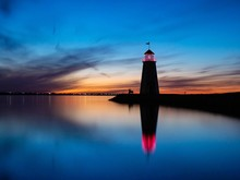 LIGHTHOUSE BY LAKE AGAINST SKY DURING SUNSET