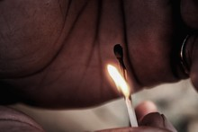 Close-Up Of Hand Holding Burning Matchstick