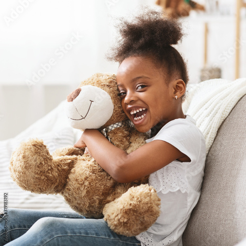 Portrait of cheerful afro girl with big teddy bear