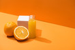Leinwanddruck Bild - fresh juice in glass bottle near oranges and white cube on orange background