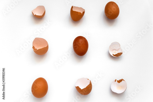 Photo top view flat lay pattern  brown eggs and egg shells on a white background